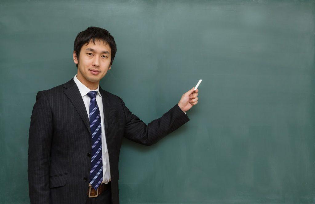 黒板で説明する男性